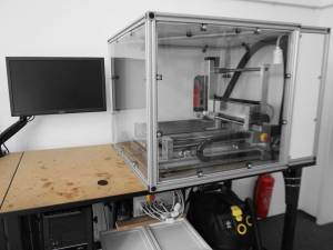The photo shows a cnc mill inside an enclosure and a computer monitor to the left. Both stand on a table. Below the table are a computer, a controller and a suction unit.