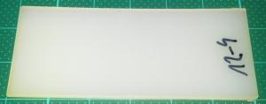 Gelbliche Biegeprobe aus Polyamid nach der Konditionierung. Sie liegt auf einer grünen Unterlage mit einem Gitter mit einem Gitterabstand von 10 mm. Die Punkte liegen in einem Abstand von 2 mm.