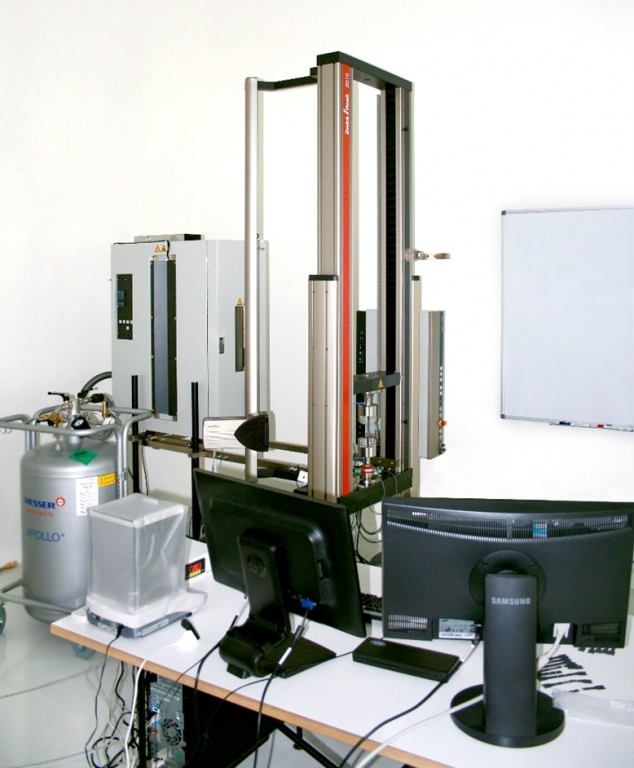 The photo shows an electro-mechanical test frame produced by Zwick. A temperature chamber and a liquid nitrogen tank are shown on the left. In the front, at the bottom, two monitors and scales stand on a table.