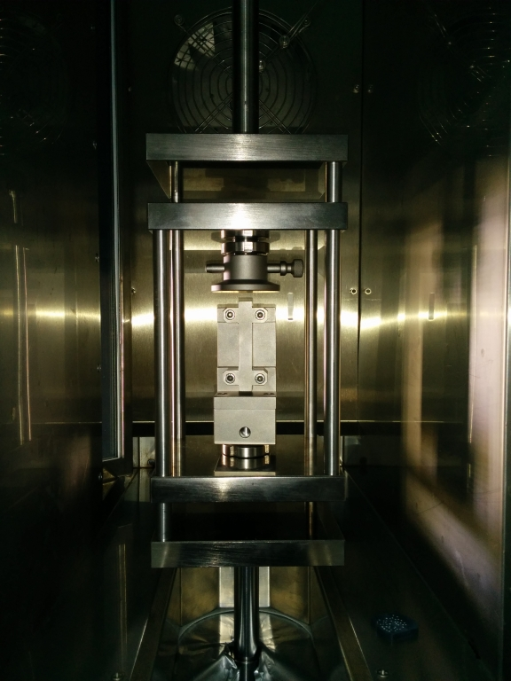 The picture shows the inside of a Zwick temperature chamber of a Zwick test frame. In the center there is a cage for load inversion. Inside the cage, there are compression platens and a support jig for rigid polymers.